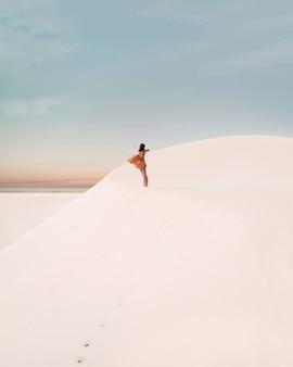 Une jolie jeune voyageuse appréciant la vie dans le désert. cette photo artistique est prise dans les dunes avec un beau coucher de soleil en arrière-plan. la fille porte une robe qui bouge au gré du vent.
