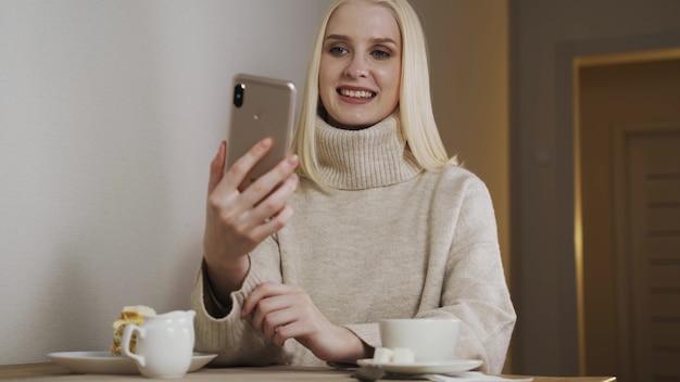 Jolie jolie étudiante jeune femme fille utilisant un téléphone portable, boire du café dans un café du soir, passer du temps en ligne à rire des messages de discussion.