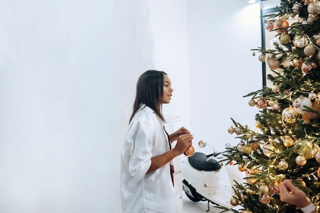 Jolie jolie femme décore le sapin de noël avec des boules