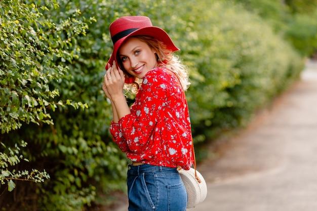 Jolie jolie femme souriante blonde élégante en chapeau rouge paille et blouse tenue de mode d'été