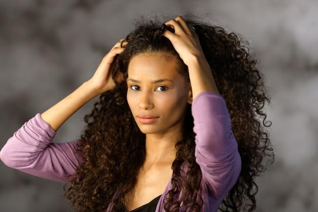 Jolie jolie fille afro-américaine touchant les cheveux