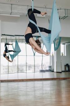 Jolie jolie fille faisant du yoga dans une pièce lumineuse
