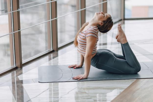Jolie jolie fille faisant du yoga et se détendre dans la salle lumineuse