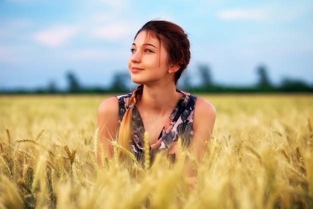 Jolie jolie jeune fille sur le champ de blé pendant le coucher du soleil
