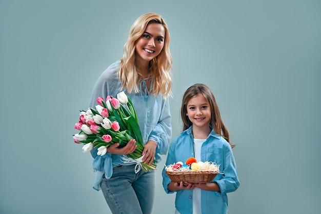 Jolie jolie maman douce et petite fille tenant un panier avec des œufs colorés et un bouquet de tulipes isolé sur un mur gris.