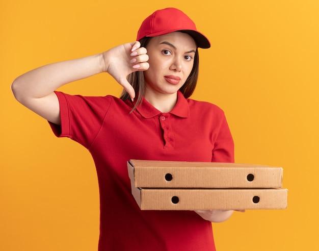 Jolie livreuse mécontente en uniforme pouces vers le bas et détient des boîtes à pizza sur orange