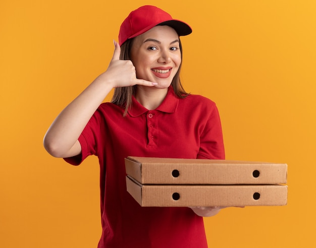 Une jolie livreuse souriante en gestes uniformes m'appelle signe de la main et tient des boîtes à pizza isolées sur un mur orange avec espace de copie