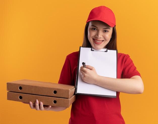 Une jolie livreuse souriante en uniforme tient des boîtes à pizza et écrit sur le presse-papiers avec un marqueur