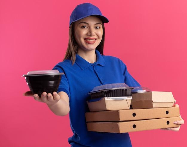 Une jolie livreuse souriante en uniforme tient un contenant de nourriture et des emballages de nourriture sur des boîtes à pizza