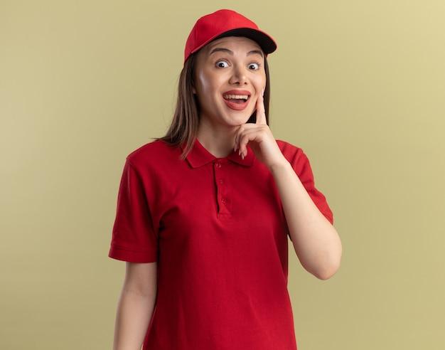 Une jolie livreuse surprise en uniforme met le doigt sur le visage et regarde la caméra