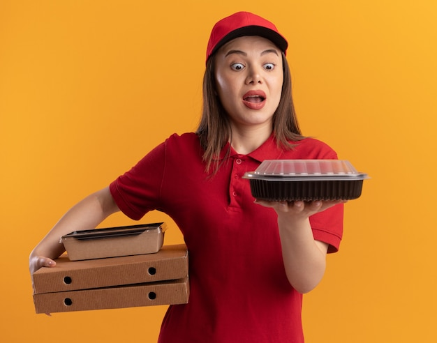 Une jolie livreuse surprise en uniforme tient un emballage de nourriture en papier sur des boîtes à pizza et regarde un récipient de nourriture isolé sur un mur orange avec un espace de copie