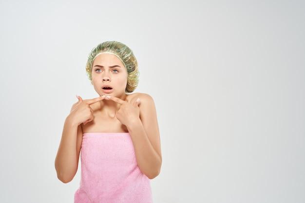Jolie lotion de femme dans le studio de problèmes de peau du visage de main