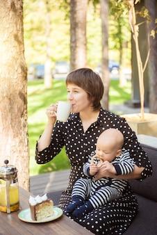 Jolie maman avec petit bébé dans un café en plein air d'été en europe