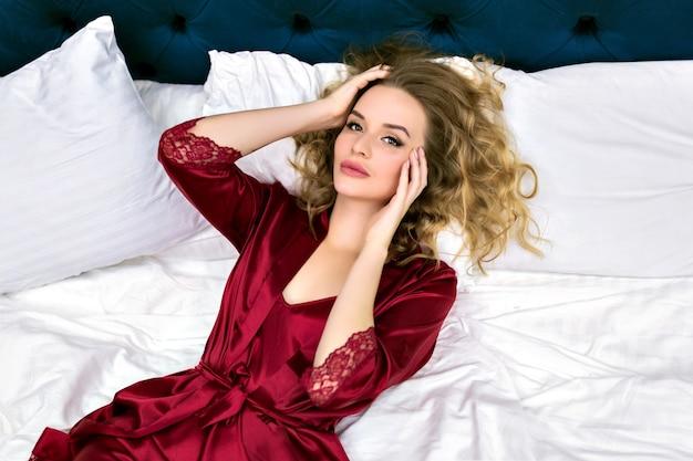 Jolie mannequin blonde sensuelle allongée sur le lit, profitez de sa matinée à l'hôtel de luxe, vêtue d'une chemise de nuit et d'un peignoir en soie bordeaux, de poils aveugles et d'un visage de beauté, style boudoir.