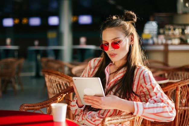 Jolie mannequin en lunettes de soleil rouges fonctionne avec sa tablette assis au café