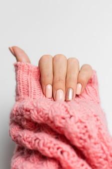 Jolie manucure de couleur nude, un doigt doré brillant, sur fond de coussin en laine rose tricoté