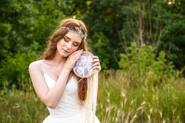 Jolie mariée aux cheveux roux tenant un capteur de rêves dans ses bras