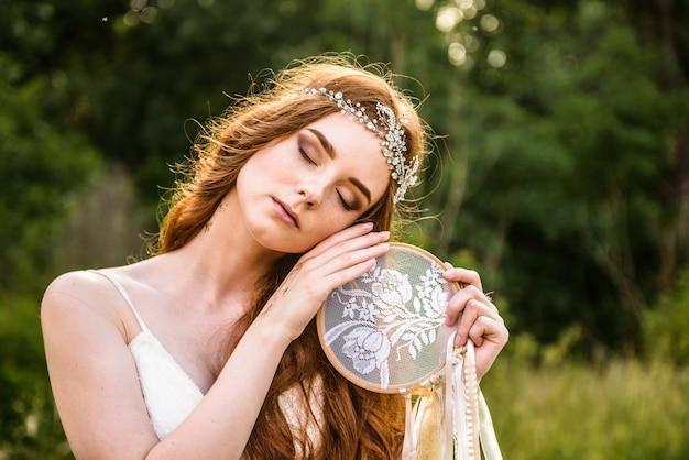 Jolie mariée aux cheveux roux touchant son visage à l'attrape-rêves