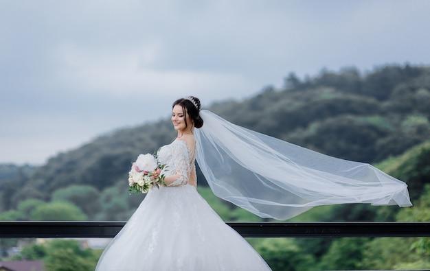 Jolie mariée caucasienne souriante avec un long voile à l'extérieur tenant un bouquet de mariée