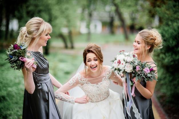 Jolie mariée et demoiselles d'honneur posent dans un parc verdoyant