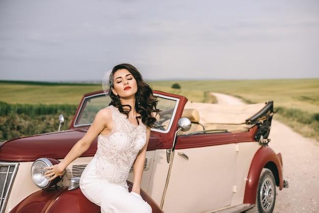 Jolie mariée élégante assise sur une voiture rétro rouge sur une route de campagne