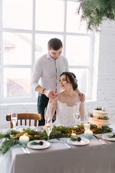 Jolie mariée et le marié près de la table de mariage avec un gâteau de mariage, des bougies bleues et des décorations en pin