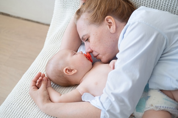 Jolie mère adulte heureuse couchée avec petit bébé. concept de garde d'enfants et de maternité. famille heureuse. profiter à la maison. l'amour.
