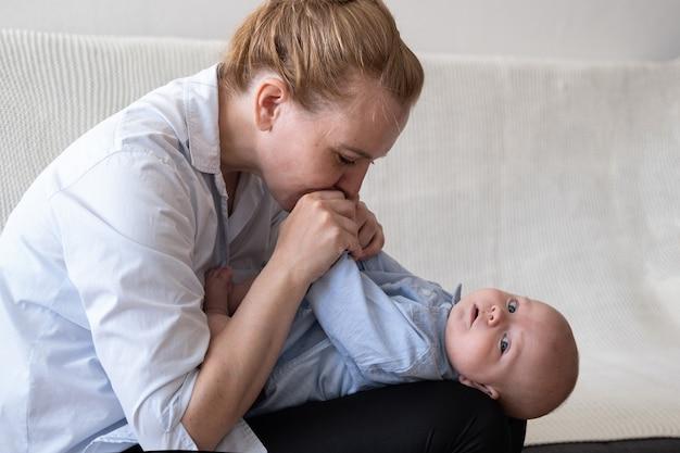 Jolie mère adulte heureuse joue baiser petit garçon.