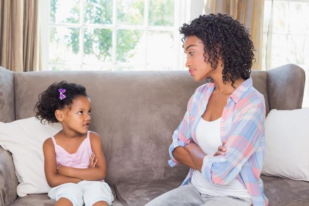 Jolie mère assise sur le canapé avec une fille pétulante