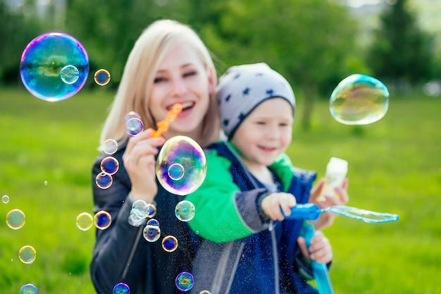 Jolie mère femme et petit garçon soufflant des bulles de savon dans le parc sur fond d'herbe verte et d'arbres.