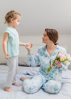 Jolie mère et fille se regardant sur le lit avec des fleurs