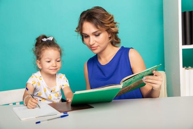Jolie mère avec une jolie fille assise avec un livre dans la chambre à la maison.