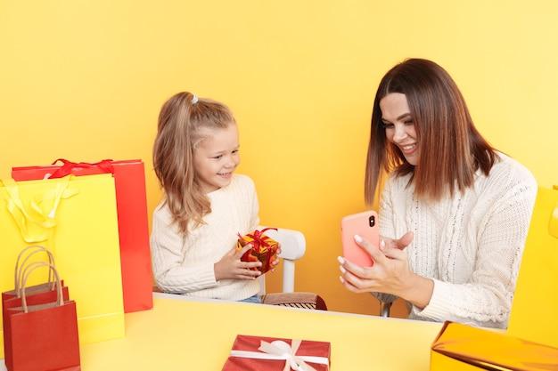 Jolie mère avec petite fille assise au bureau avec des cadeaux et utilisant le téléphone pour choisir des cadeaux en ligne.