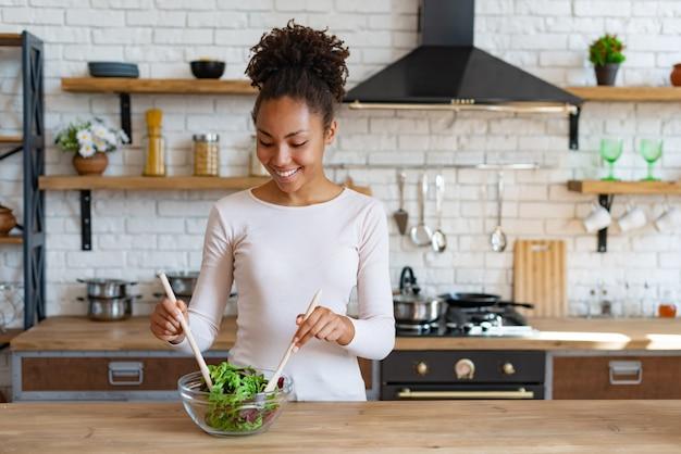 Jolie mulâtre ménage cuisiner à la maison un aliment sain - salade