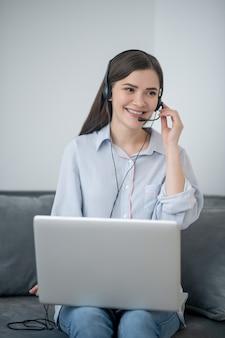 Une jolie opératrice aux cheveux noirs du galop d'appel travaillant à domicile