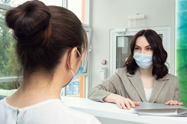 Une jolie patiente parle à l'administrateur près du comptoir
