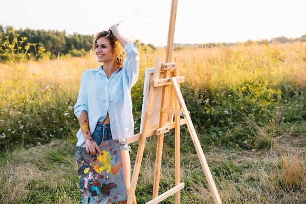 Jolie peintre talentueuse peignant sur chevalet, faisant des croquis colorés, créant un paysage marin. belle peinture d'artiste féminine avec des peintures à l'aquarelle. concept de créativité et d'imagination.