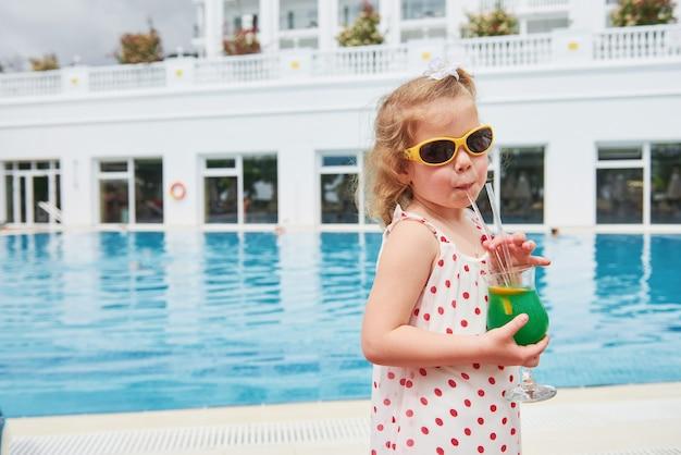 Jolie petite blonde à la piscine et tenant le cocktail d'un enfant.