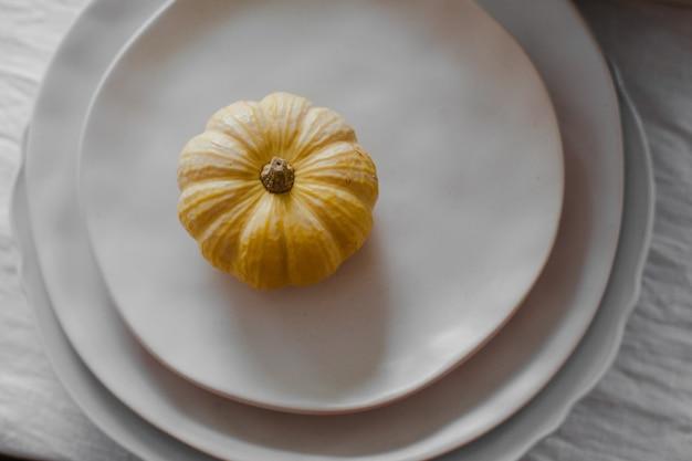 Jolie petite citrouille jaune placée sur le dessus d'une pile d'assiettes sur la table