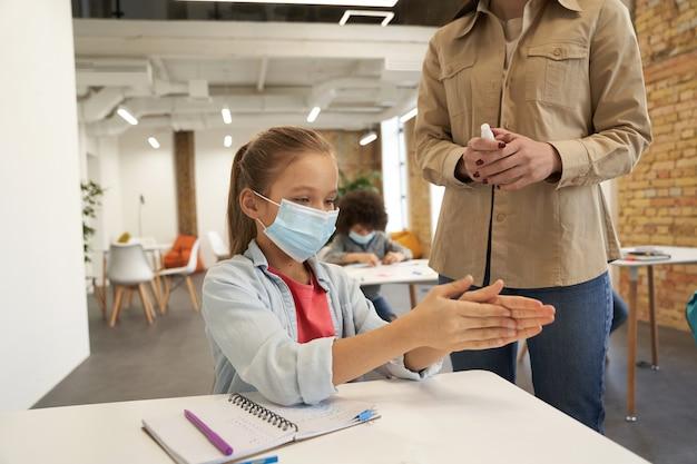 Jolie petite écolière portant un masque de protection nettoyant ses mains enseignante à l'aide d'un