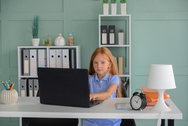 Jolie petite étudiante faisant ses devoirs à la maison en ligne