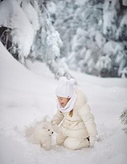 Jolie petite fille de 4 ans avec un chiot blanc moelleux dans la forêt d'hiver