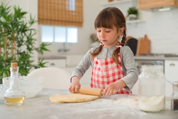 Jolie petite fille de 4 ans avec des nattes déroule la pâte avec un rouleau à pâtisserie sur la table de la cuisine.