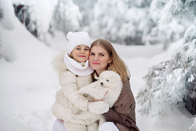 Jolie petite fille de 4 ans et sa belle mère avec un chiot blanc moelleux dans la forêt d'hiver