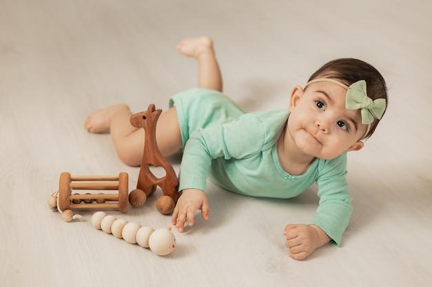 Une jolie petite fille de 8 mois se trouve sur le plancher en bois de la maison en jouant avec des jouets de développement en bois. photo de haute qualité