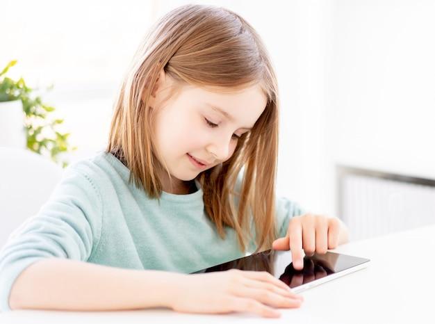 Jolie petite fille à l'aide de tablette