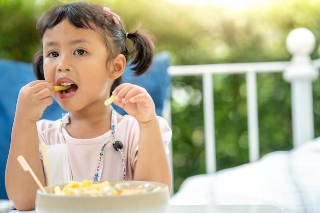Jolie petite fille aime manger des frites pour le déjeuner en plein air
