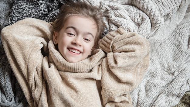 Jolie petite fille amusante dans un pull en tricot