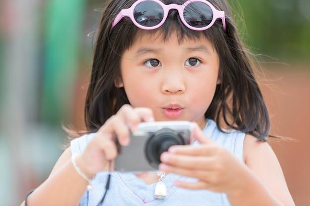 Jolie petite fille avec un appareil photo numérique compact se sent incroyable avec sa photo de voyage en thaïlande