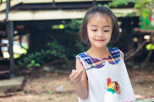 Jolie petite fille apprend joyeusement en dehors de la salle de classe avec une nature magnifique et un sourire éclatant